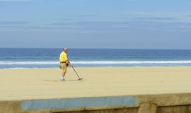 Metal detectorist on Pacific Beach. An old man walking along the coast holding a portable metal detector on the Pacific beach in America, pointing the long stick royalty free stock photo