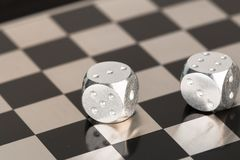 Metal dice on a chessboard. In the photo you see metal dice on a chessboard Royalty Free Stock Image