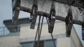 Metal dirty excavator laddle with attached chains at building site stock video