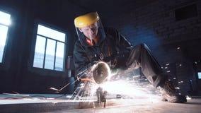 Metal do corte do homem usando a máquina de moedura Fotos de Stock
