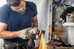 Metal do moedor do homem um moedor de ângulo Imagem de Stock Royalty Free