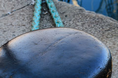 Metal dock with a ship rope in harbor. Stock Photography