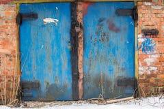 Metal door of garage with lock. brick background Royalty Free Stock Photo
