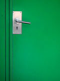 Metal door handle on green Royalty Free Stock Image