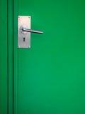 Metal door handle on green royalty free stock image