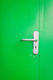Metal door handle on green steel door Stock Photography