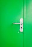 Metal door handle on green steel door Stock Photography