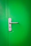 Metal door handle on green steel door Royalty Free Stock Photos