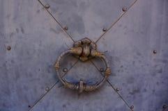 A metal door handle on a grey metal door stock photos