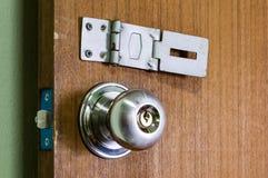 Metal door handle and lock. Close up metal door handle and lock on a wooden door Royalty Free Stock Photos