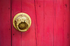Metal door knocker on wooden door pink background.  Royalty Free Stock Photos