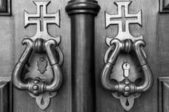 Metal Door Knockers on Wooden Door with Crosses Stock Photo