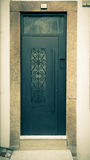 Metal door with patterns on the stone wall. Toned Royalty Free Stock Images