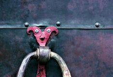 A metal door with a playful handle in the form of a jester. Old metal, rusty door of different colors Royalty Free Stock Image