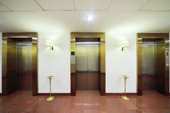 Metal doors to elevators. Marble floor and high ashtrays in big stylish hotel stock illustration