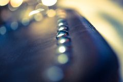 Metal Dot row on black leather with bokeh and Stock Photography
