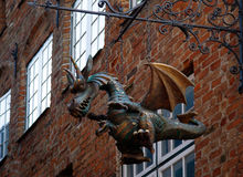 Metal dragon hanging from the brick wall Royalty Free Stock Photography