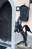 Metal dragon statue, Slovenia. Metal dragon statue chained to outside building wall in Slovenia village Royalty Free Stock Images