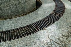 Metal drain cover. Image of Rusty metal drain cover with gray granite floor Royalty Free Stock Photos