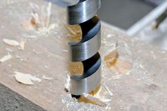 Metal drill drills a hole in wooden bar. stock photography