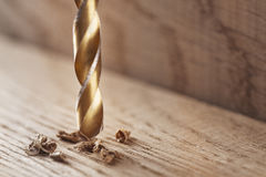 Metal drill makes a hole in the wooden oak table with wood shavi. Ngs Stock Photo