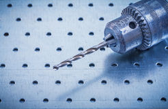 Metal drill on perforated metallic background Royalty Free Stock Photos