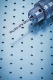 Metal drill on perforated metallic sheet Stock Image