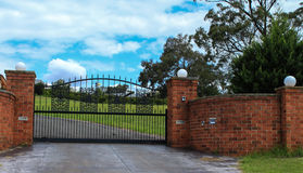 Metal driveway entrance gate set in brick fence. Black wrought iron entrance gate set in brick fence Stock Photo