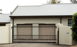 Metal driveway entrance gates set in brick fence. Brown metal driveway entrance gates with double car garage Royalty Free Stock Photos