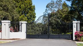Metal driveway entrance gates set in brick fence with garden trees in background. Black Metal driveway entrance gates set in brick fence with garden trees in Stock Photo