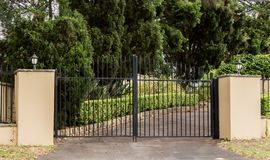 Metal driveway entrance gates set in brick fence with garden trees in background. Metal driveway entrance gates set in brick fence with garden trees Royalty Free Stock Photography