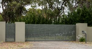 Metal driveway entrance gates set in brick fence leading to rural property with eucalyptus trees in background. Metal driveway entrance gates set in brick fence Royalty Free Stock Photography