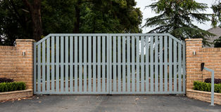 Metal driveway entrance gates set in brick fence. Security driveway entrance gates set in brick fence with garden trees in background Stock Photo