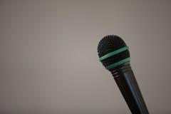 Metal drucianej siatki czerni mikrofon na szarym tle Zdjęcie Stock