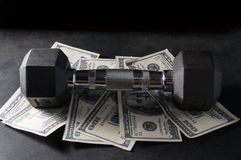 Metal dumbbell on money. Royalty Free Stock Images