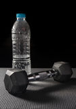 Metal dumbbell with water bottle. Stock Images