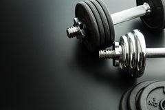 The metal dumbbell and weights. The metal dumbbell and weights on black background Royalty Free Stock Images
