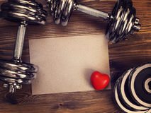 Metal dumbbells and red heart on a wooden background. Toned image of metal dumbbells and a red heart on a wooden background stock photo