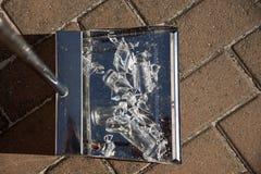 Metal dustpan containing broken glass Stock Photo
