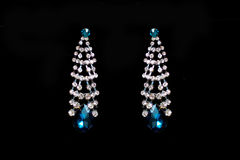 Metal earrings with blue stones. On a black background Stock Photography