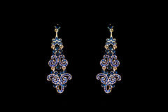 Metal earrings with blue stones. On a black background Stock Image