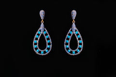 Metal earrings with blue stones. On a black background Royalty Free Stock Images