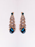 Metal earrings with blue stones. On the white background Stock Image