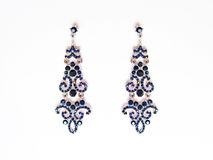 Metal earrings with blue stones. On the white background Stock Photo