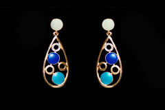 Metal earrings with colored stones. On a black background Stock Images
