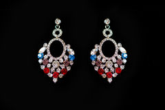 Metal earrings with colored stones. On a black background Stock Photography