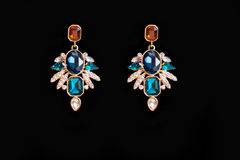 Metal earrings with colored stones. On a black background Stock Image
