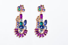 Metal earrings with colored stones. On a white background Stock Photography