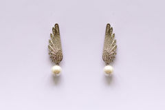 Metal earrings with pearls. On a white background Stock Photo