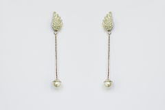 Metal earrings with pearls. On a white background Stock Image